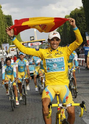 Three-time Tour de France winner Alberto Contador of Spain holds aloft the Spanish national flag during a victory lap with his Astana teammates after the 20th and last stage of the Tour de France cycling race over 102.5 kilometers (63.7 miles) with start in Longjumeau and finish in Paris, France, Sunday, July 25, 2010.