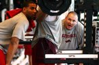 Razorback football Head Strength and Conditioning Coach Jason Veltkamp (R) gives encouragement to player Khiry Battle as he does leg exercises Thursday, March 5, 2009 in the weight room at the indoor practice facility on the University of Arkansas campus in Fayetteville.  Spotting is Freddy Burton (L).