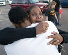 Shamecca Davis hugs her son Isaiah Bow, who was an eye witness to the shooting, outside Gateway High