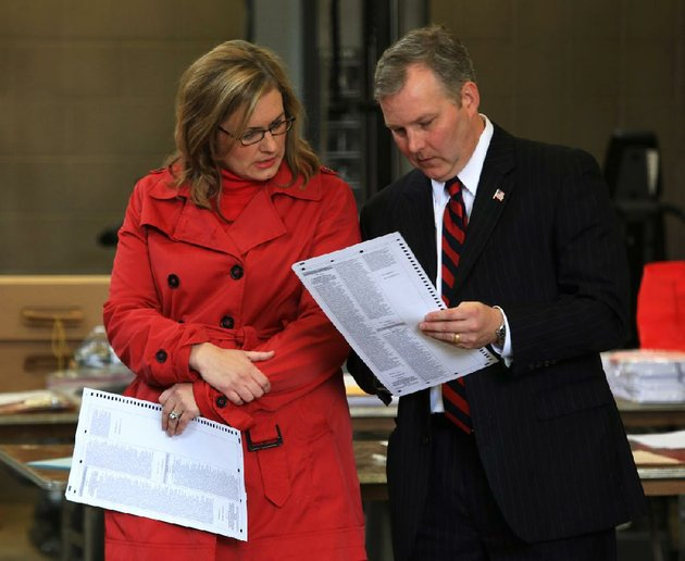 file-u-s-rep-tim-griffin-right-and-his-wife-elizabeth-look-at-a-ballot-while-waiting-to-vote-the-morning-of-nov-6-2012-in-little-rock
