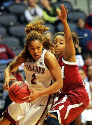 UALR guard Taylor Ford (left) drives to the basket past Troy's Ashley Beverly-Kelley during their game Thursday night at the Jack Stephens Center. Ford finished with 12 points, 9 rebounds and 8 assists in the Trojans' 75-52 victory.