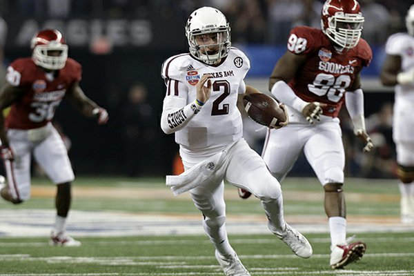 Texas A&M's Johnny Manziel (2) finds running room as Oklahoma's Javon Harris (30) and Chuka Ndulue (98) give chase in the first half of the Cotton Bowl NCAA college football game Friday, Jan. 4, 2013, in Arlington, Texas. (AP Photo/LM Otero)