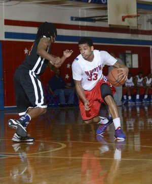 Little Rock Parkview's Anton Beard (33) tries to dribble around Little Rock Hall defender Javon Perry during the Patriots' 57-52 loss Tuesday at Charles Ripley Arena in Little Rock.