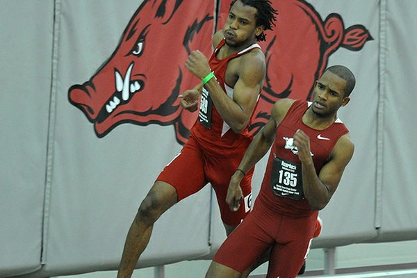 NWA Media/MICHAEL WOODS --01/25/2013-- Arkansas runner Akheem Gauntlett (front) and Nebraska runner Dexter McKenzie round the last turn in the men's 200m run during Friday night's action in the Razorback Invitational at the Randal Tyson Track Center in Fayetteville.
