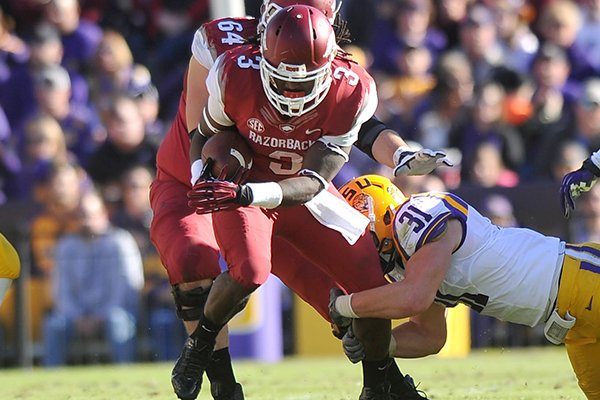 Arkansas running back Alex Collins runs the ball during the first quarter of Friday afternoon's game at Tiger Stadium in Baton Rouge, La.