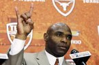 "Charlie Strong holds up the ""Hook'em Horns"" hand signal during an NCAA college football news conference where he was introduced as the new Texas football coach, Monday, Jan. 6, 2014, in Austin, Texas. Strong acknowledged the historical significance of being the school's first African-American head coach of a men's sport. He takes over for Mack Brown, who stepped down last month after 16 seasons. (AP Photo/Eric Gay)"