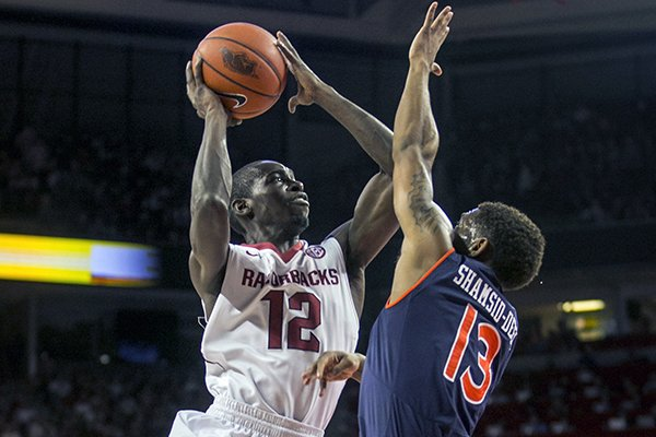 Arkansas guard Fred Gulley III (12) drives to the basket against Auburn guard Tahj Shamsid-Deen (13) during the first half of an NCAA college basketball game on Saturday, Jan. 25, 2014, in Fayetteville, Ark. (AP Photo/Gareth Patterson)