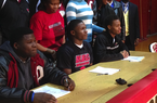 Flanked by teammates, Pine Bluff Dollarway athlete Josh Liddell (center) waits at a signing ceremony Wednesday, Feb. 5, 2013, in the Dollarway High School gym. Liddell signed with Arkansas.