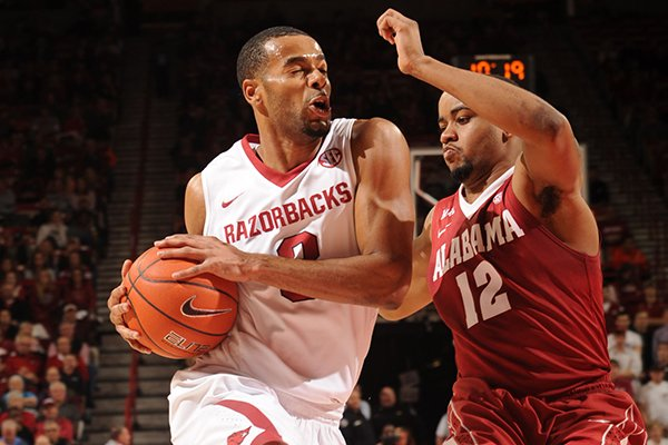 Arkansas senior Rickey Scott, left, drives to the lane as Alabama senior Trevor Releford defends during the first half of play Wednesday, Feb. 5, 2014, in Bud Walton Arena in Fayetteville.