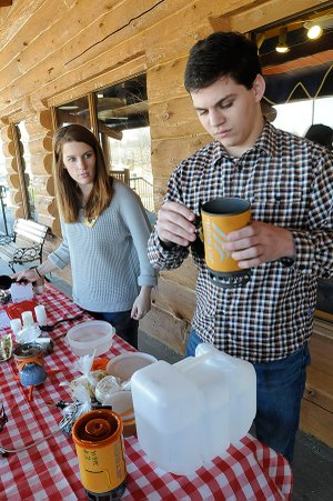 Miriam Daniel, left, and Hugh Brewer whip up some oatmeal in a backpack-style stove.