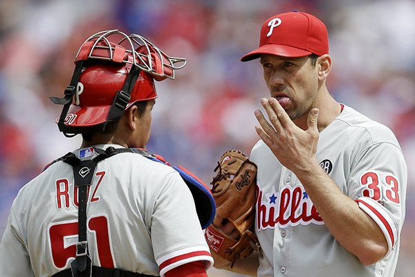 Philadelphia Phillies catcher Carlos Ruiz (51) and starting pitcher Cliff Lee (33) conference during the fifth inning of an opening day baseball game against the Texas Rangers at Globe Life Park, Monday, March 31, 2014, in Arlington, Texas. (AP Photo/Tony Gutierrez)