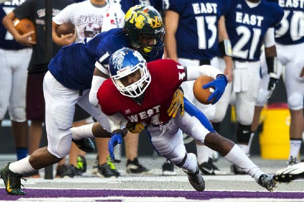 Arkansas Democrat-Gazette/MELISSA SUE GERRITS - 06/27/2014 -  East's Jaylen Clark, brings down West's Devonte Howard during the High School All Star football game June 27, 2014 at UCA in Conway.