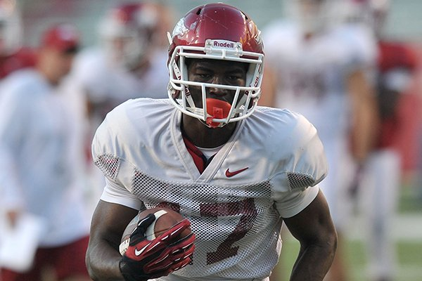 Arkansas receiver JoJo Robinson runs with the football during a practice Wednesday, Aug. 13, 2014 at Razorback Stadium in Fayetteville.