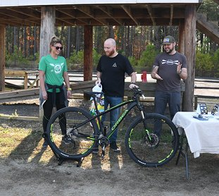 The Sentinel-Record/Mara Kuhn - Heath Netzley of Little Rock, center, accepts prizes for Darren Houston of Little Rock, as Drea Poteete, owner of Spa City Cycling, left, and Brian Marcus, with Local Arkansas, look on at Cedar Glades Park on Saturday, Dec. 2, 2017. Houston won the Natural Arkansas November photography contest on Instagram.
