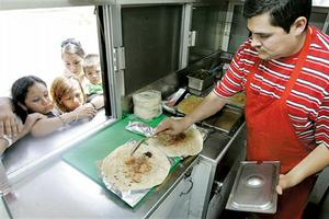 Jorge Campos (right) prepares food for customers at Taqueria Samantha.