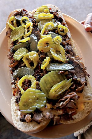 Famous Philadelphia Cheese Steak topped with pickles that might put off purists at Philam Gourmet on South University Avenue in Little Rock.