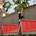 Shawn Jenkins with Phil Potts Extreme Painting in Bentonville paints along the roofline Monday on th...
