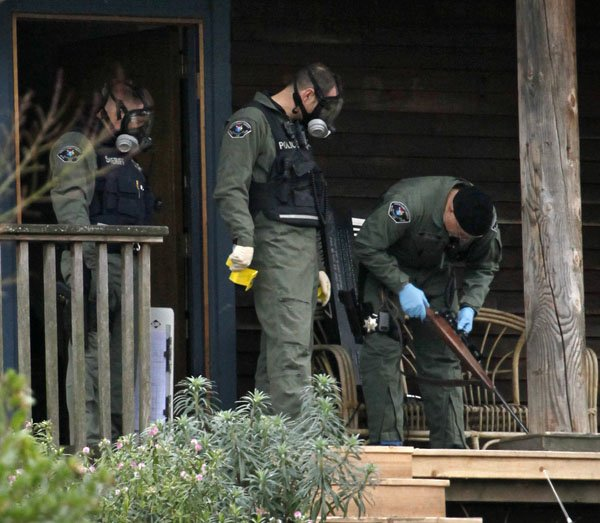 sheriffs-deputies-look-over-a-rifle-they-removed-from-a-home-where-a-suspect-in-the-slaying-of-four-police-officers-gunned-down-a-day-earlier-was-believed-to-have-been-monday