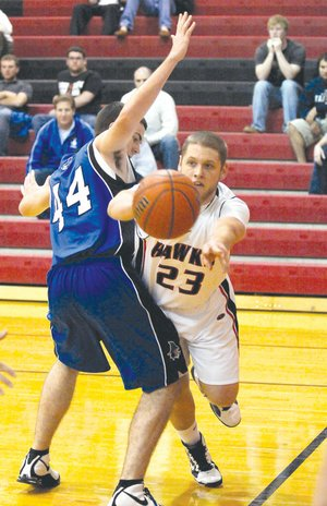 Rea Ridge Blackhawk forward Cameron Thompson, No. 23, passed under Rogers Mounties post Nathan Musso, No. 44, in a home game in November.