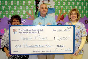Justin Bradford, center, of the Pea Ridge Optimist Club, presented a check for $1,000 to Cheryl Tillman, left, and nurse Val Colburn, right, for Heart and Soul, an organization to minister to children's needs.