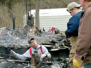 Benton County fire marshal Will Hanna searches for evidence with Sheriff's investigator Jeremy Felton as they sift through the ashes at the former home of Jeremiah and Samantha Cotton. Watching is Jeremiah's maternal grandfather, Gary Fletcher, who built the house in 1995.