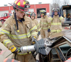 Pea Ridge Fire Department Captain Brian Johnson illustrated the use of the Jaws of Life cutting tool to Pea Ridge firefighters during a training event Saturday, March 13. Watching were Brian Cogdill, Jeremy Hanna and Justin Collins.