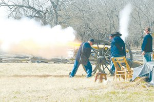 Members of the Northwest Arkansas Historical Association fire a canon Saturday near Elk Horn Tavern at Pea Ridge National Military Park.