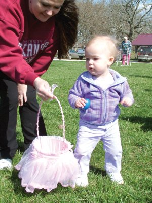 Morgan Ivy, 15 months, hunted Easter eggs at the annual Beta Alpha Sorority Easter Egg Hunt Saturday, March 27, at Pea Ridge City Park assisted by her mother, Jennifery Ivy. She is the daughter of Shannon and Jennifer Ivy. Dorothy Williams, a charter member of Beta Alpha, is in the background.