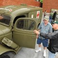 Jim Sanders, center of Baytown, Texas, shows his 1942 Dodge ambulance on Friday to Everett Avery of...