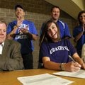 CASEY AT THE SIGNING DESK - Rogers High's Johanna Casey, center, reacts from the applause of her tea...