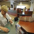 MAKING A DEPOSIT - Caroline Lennox of Fayetteville fills out a deposit slip Thursday at UARK Credit ...
