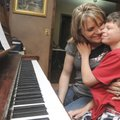 Tayden Larsen, 10, gives mother Casey Larsen a hug Friday while practicing the piano at the family's...