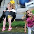 Avery Ainley, 4, right, pushes her sister, Emery Ainley, 18 months, on a swing Sunday at Dave Peel P...