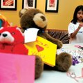 Marisa Fontana, 8, of Rogers makes a ribbon decoration Sunday while collecting teddy bears for Opera...