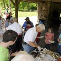 Steve Embrey with the Rogers Noon Kiwanis serves children Wednesday at the Kiwanis' annual picnic fo...