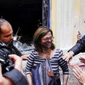 A bank employee reacts after being rescued from a fire that broke out when the bank was attacked dur...