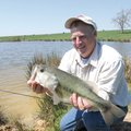 Ronnie Bell admires a 6-pound largemouth bass he caught from one of the ponds on his farm near Hinds...