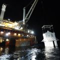 The containment vessel is lowered into the Gulf of Mexico on Thursday at the site of the Deepwater H...