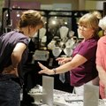 Karen Lockhart, middle, tries on a ring Friday as Marge Brown, right, and Rhonda Manichia, left, own...