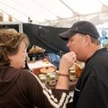 Bentonville High School football coach Rick Rachel gets a bite of a pickled treat Saturday from wif...