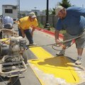 Duston Daniels, right, and Donny Wall, both with Marking Systems of Springdale, paint traffic arrows...