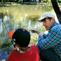 Jeff Courtway gives a few fishing pointers to a child Saturday at the Hooked on Fishing not Drugs an...