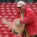 Facilities Supervisor for softball Kevin Jones spreads conditioner over the infield at Bogle Park af...