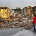 Ann Powell calls her insurance company on Monday while standing in front of what is left of her hous...