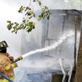 Firefighters hose down the remains of a house destroyed by fire about 11 a.m. Monday on Colonel Meye...