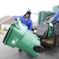 Anthony Rodriguez, left, with Rehrig Pacific Company, carries a new Waste Management cart to a Sprin...