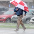 Joey Nelson sprints across Southwest Eighth Street during heavy morning rain in Bentonville on Frida...