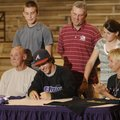 Elkins' Hunter Guffey, center, signs a national letter of intent Wednesday to play basketball for th...