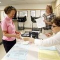 Linda Bruce, left, of Bella Vista checks in with election officials Kim Stevens of Rogers and Nancy ...