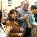 New U.S. citizens celebrate Friday after a naturalization ceremony at Bentonville Public Library. Th...